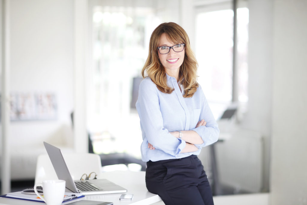 businesswoman happy sitting on her desk with her arms crossed
