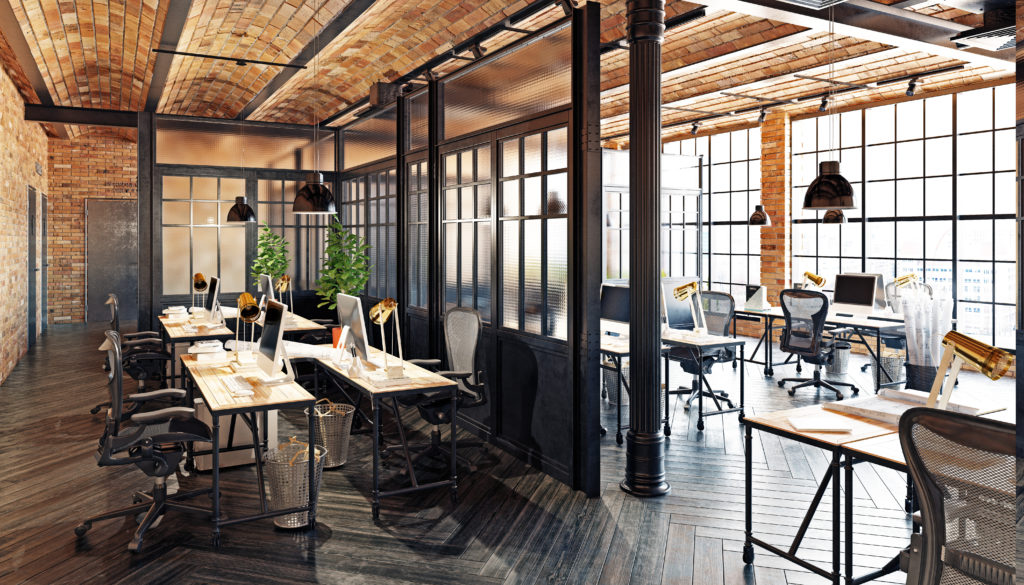 Still of the interior of a modern office aligned with wooden features, divided work spaces, office chairs, and office tables.