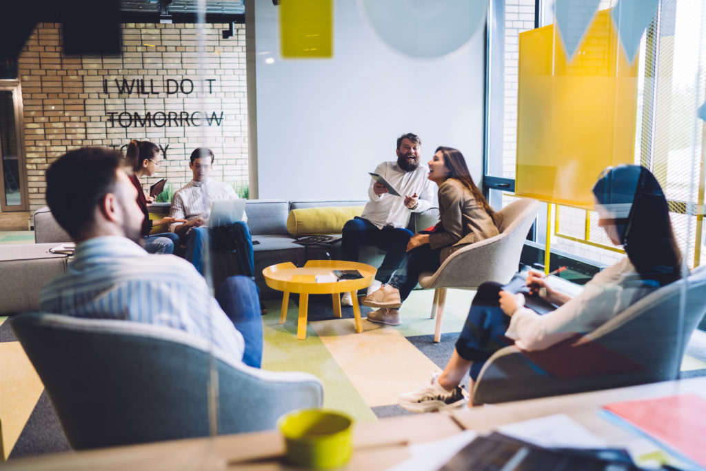 Group of joyful and cheerful coworkers sitting together in bright creative office and laughing while discussing launch of new project of company