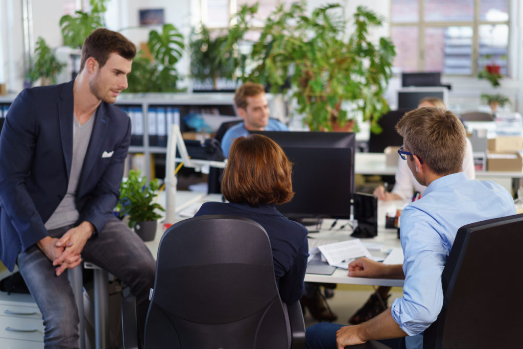 a group of young employees collaborating in a shared work space